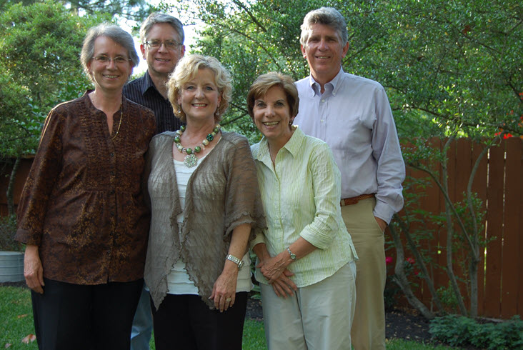 A portrait of 5 adults standing outside.